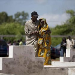 A woman is assisted by a nearby man after being overcome with grief while visiting a cemetery containing 140 unmarked graves of victims of the 2002 Joola ferry disaster in Mbao, outside Dakar, Senegal on Wednesday, Sept. 26, 2012, the tenth anniversary of the ferry's sinking. With an official death toll of 1,863 and only 64 survivors, the Joola disaster remains one of the deadliest in maritime history, surpassing by a large margin the death toll of roughly 1500 in the 1912 sinking of the Titanic.