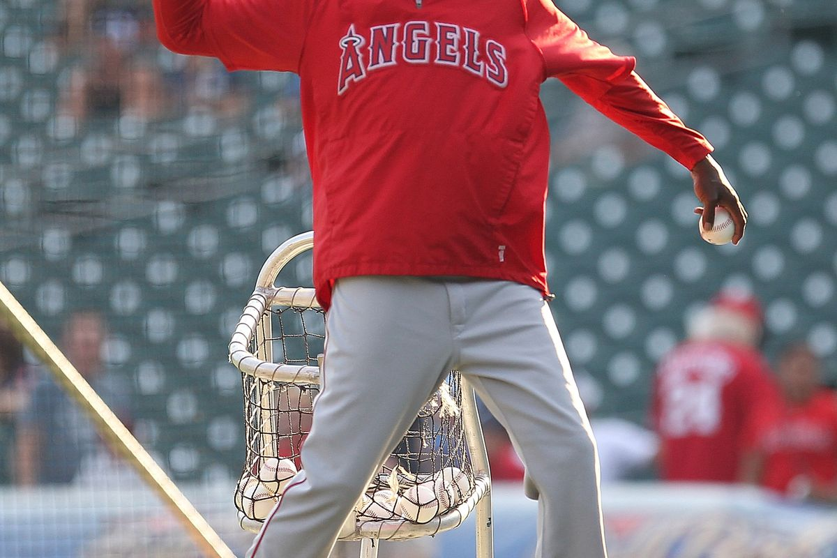 First base coach Alfredo Griffin #4 of the Los Angeles Angels of Anaheim pitches the baseball in batting practice before a MLB game against the Detroit Tigers at Comerica Park on August 24, 2012 in Detroit, Michigan.