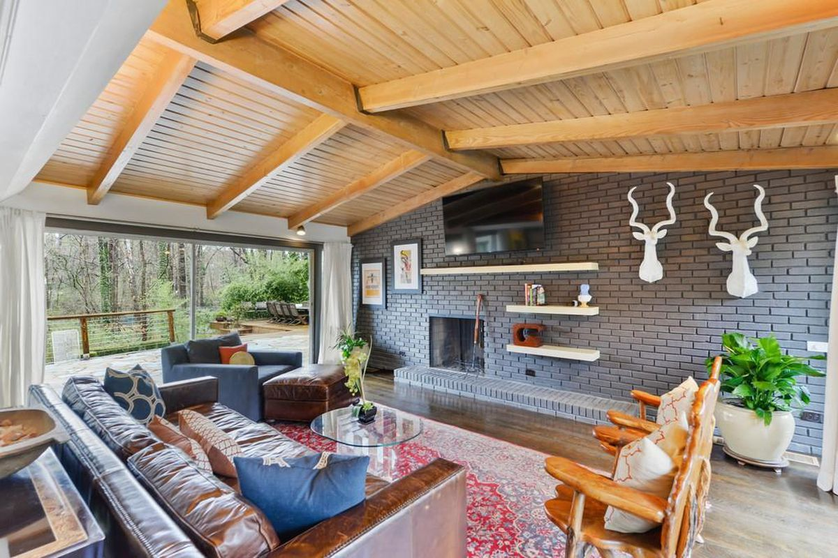 A midcentury modern living room with a fireplace and tongue-and-groove wooden ceiling with leather furniture.