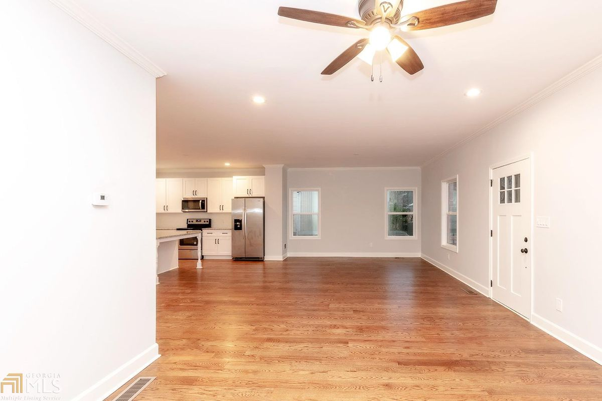 Open floorplan with ceiling fan in foreground and kitchen in the background on the left.