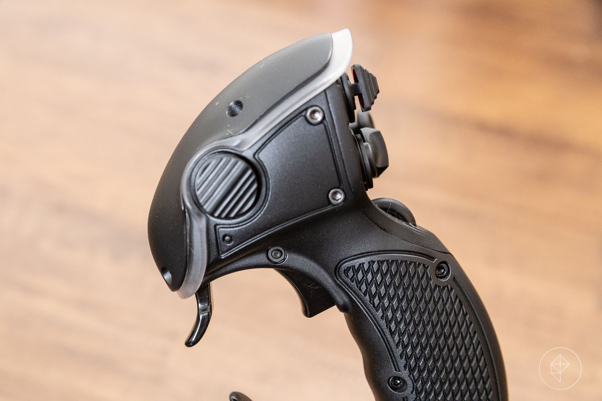 A close-up of a flight stick showing the trigger mechanism.