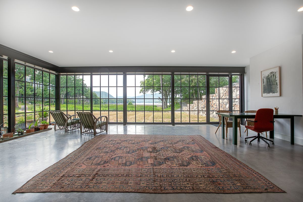 An open room features walls of glass on two sides, recessed lighting, and a rug with limited furniture: just  desk and two lounge chairs.