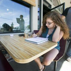 Taylor Holt works on her drawings while spending time at the Coffee Pod Friday, Aug. 2, 2013. Holt applied this summer to be accepted into the BYU animation program. It was her second and final chance.