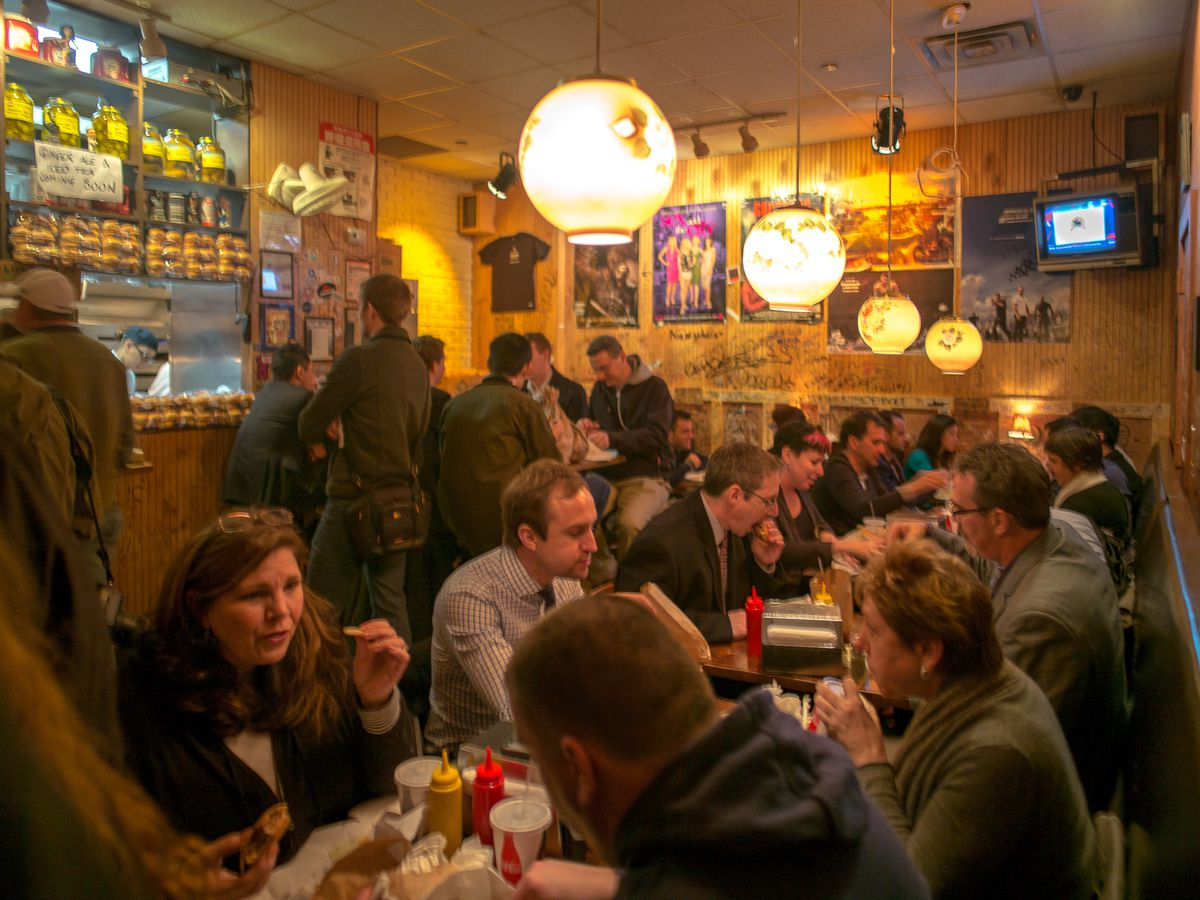 Diners feast on burgers at the crowded Burger Joint at the Parker hotel