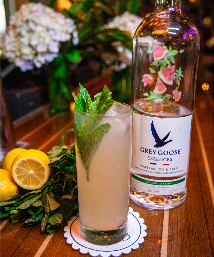 A pink cocktail with sprigs of mint on a wooden bar