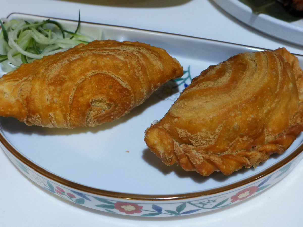 A pair of half moon hand pies with a curious spiral appearance to the dough.