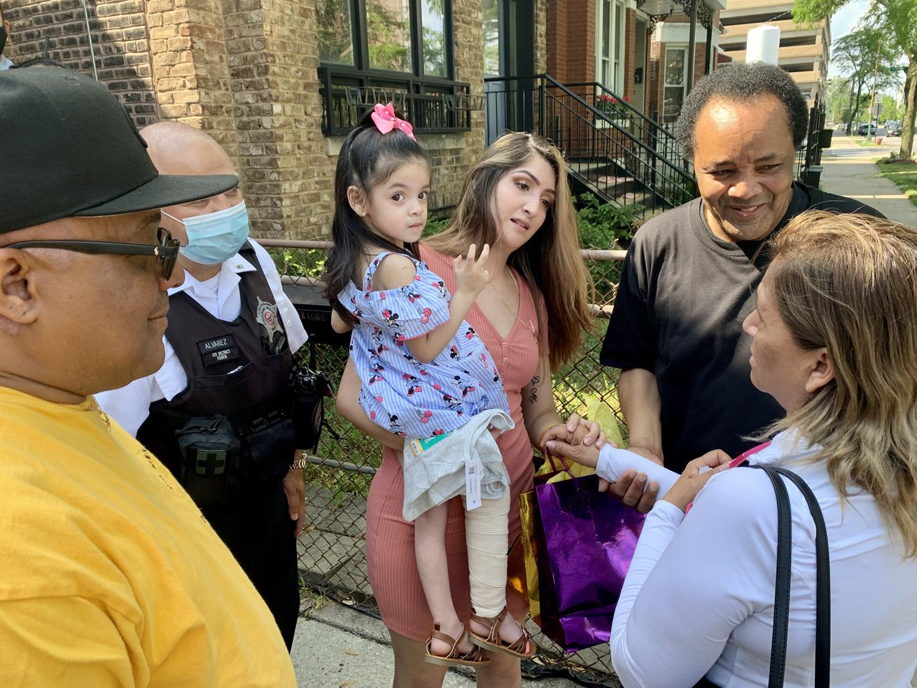Angelina Rodgriguez is held by her mother Perla Rodgriguez Saturday outside their West Side home.