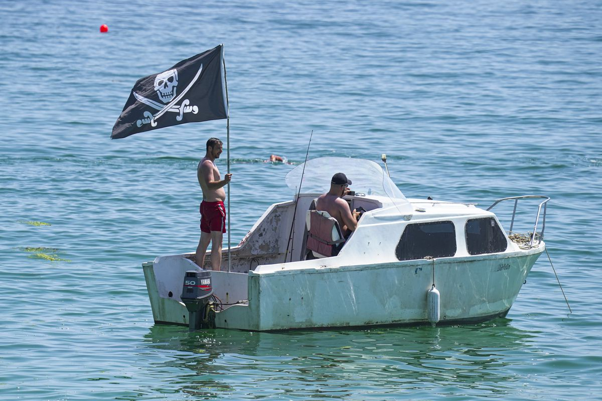Holiday makers float in a boat with a pirate flag near Gyllyngvase Beach on July 17, 2021 in Falmouth, United Kingdom