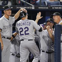 Colorado Rockies' Jordan Pacheco (22) is greeted by manager Jim Tracy, left, and and others after hitting a solo home run in the fifth inning of a baseball game against the Atlanta Braves on Tuesday, Sept. 4, 2012, in Atlanta.