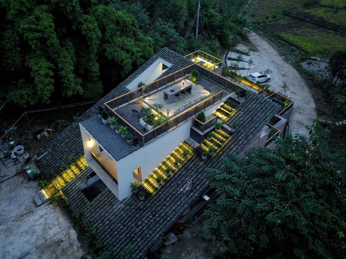 Aerial shot of home's roof with a terrace surrounded by stairs cutting through a tiled roof.