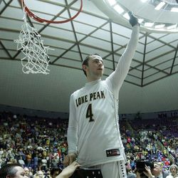 Lone Peak's Nick Emery celebrates by cutting down the net after their win over Alta in the 5A State Championship game in Ogden Saturday, March 2, 2013.