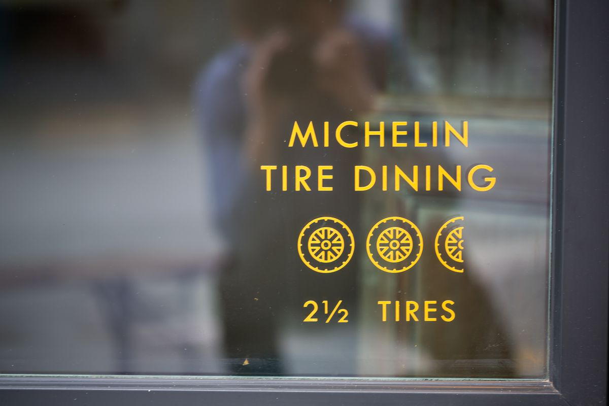 """A shot of the front window with decal sign reading """"Michelin Tire Dining"""" and 2 and half tires at Little Bear in Summerhill Atlanta"""
