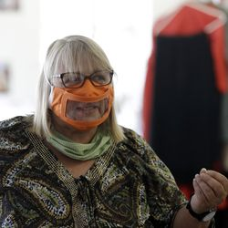 Ingrid Helton, costume director for the San Diego Opera, talks while wearing one of her mask prototypes with a window in San Diego.