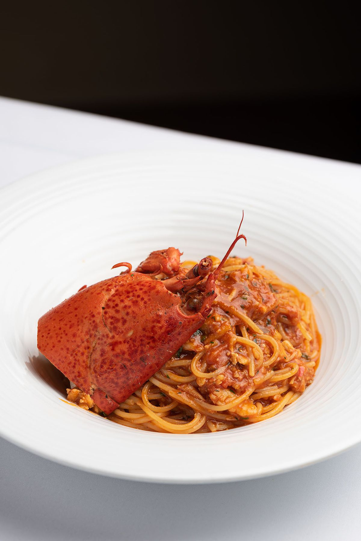 A long noodle lobster pasta lit from above.
