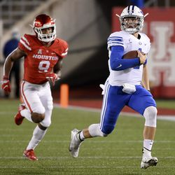 BYU quarterback Zach Wilson, right, runs past Houston safety JoVanni Stewart during the first half of an NCAA college football game on Friday, October 16, 2020 in Houston.