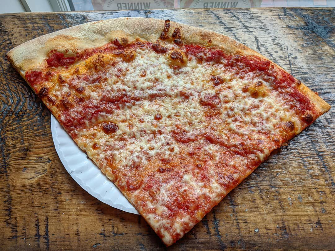 Overhead view of a giant slice of cheese pizza on a paper plate on a wooden counter