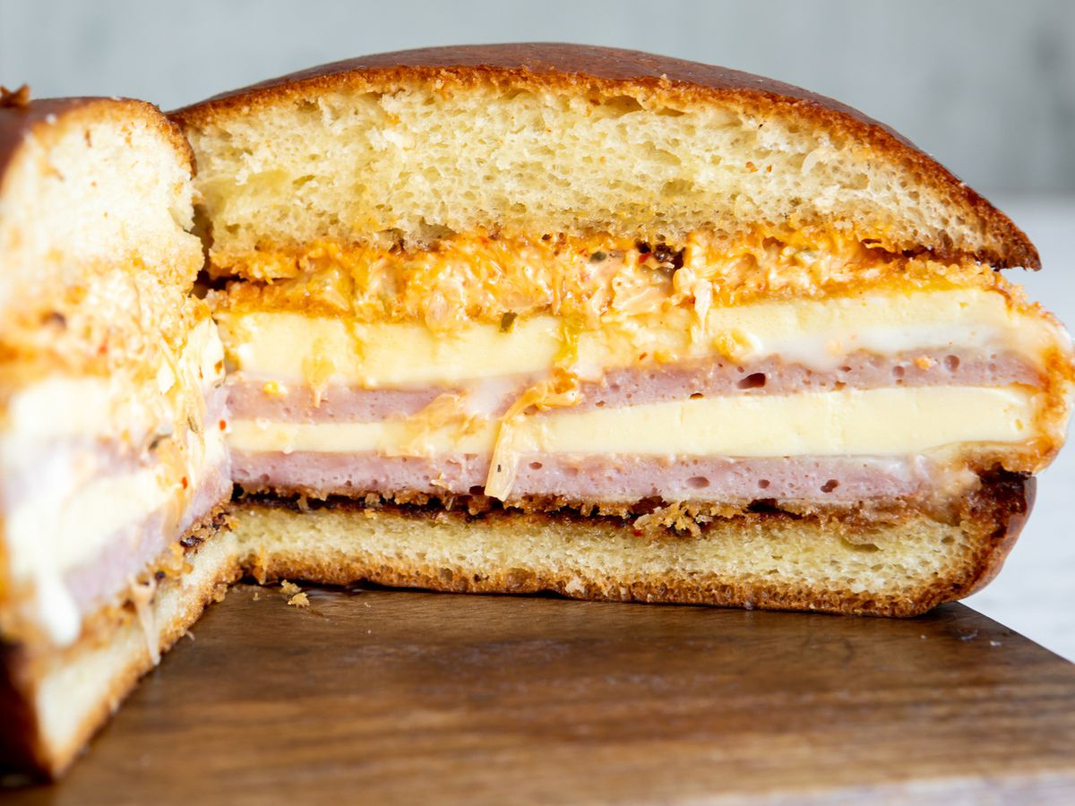 A cross section of the breakfast sandwich reveals layers of Spam, steamed egg, and melted cheese