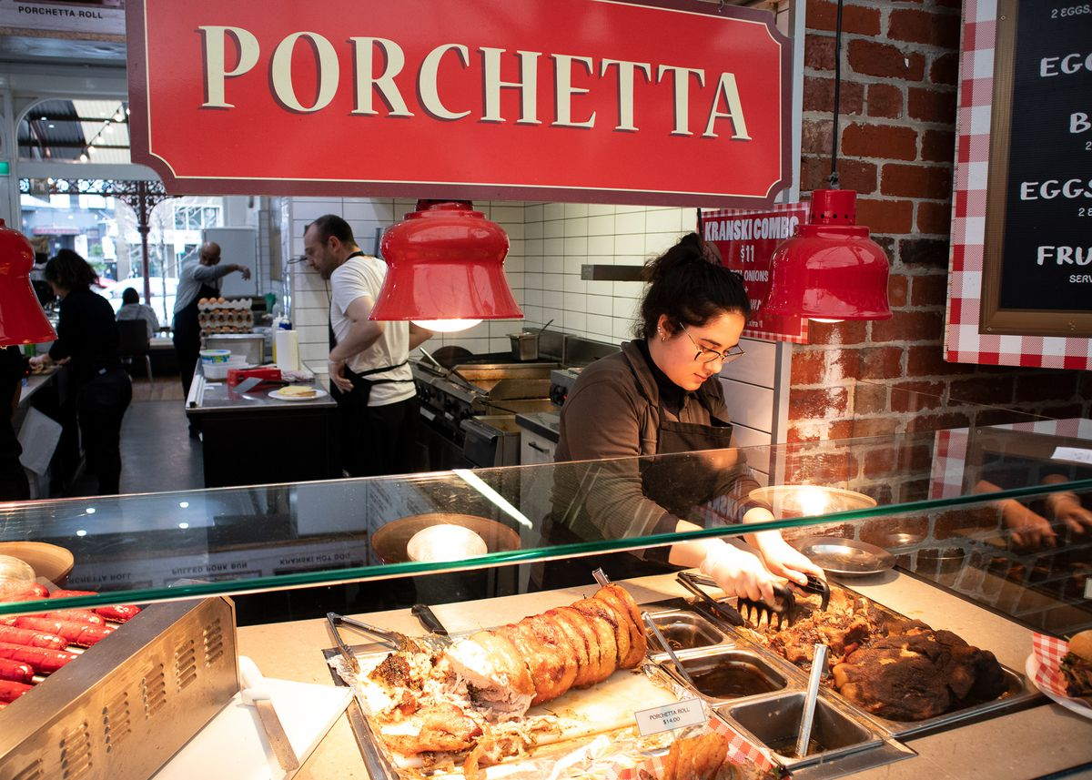 A woman dishes out porchetta from the case at Cafe Verona