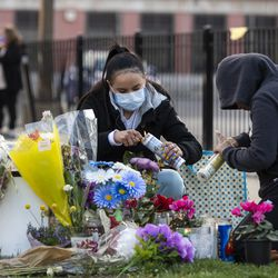 Two women from the Little Village community tend to the memorial for Adam Toledo, located near 24th St. and Sawyer Ave. Thursday, April 15, 2021 in Chicago. Adam Toledo, a 13-year-old Chicago boy appears to have dropped a handgun and begun raising his hands less than a second before a police officer shot and killed him last month, footage released Thursday under community pressure shows.