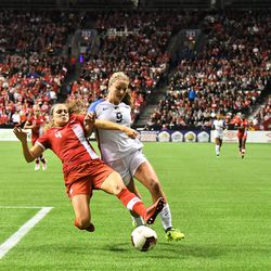 Lindsey Horan and Shelina Zadorsky go all-in for a ball at the endline.