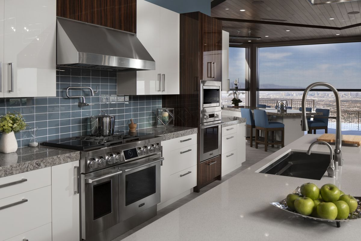 A well appointed kitchen with blue tile and high-end appliances is shown with a striking view of Las Vegas in the distance.