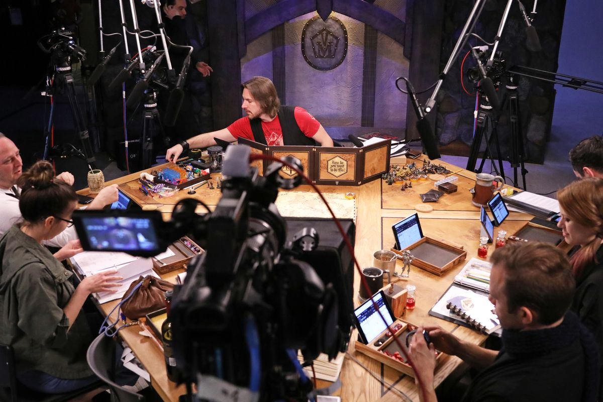 The team at Critical Role at the table surrounded by cameras.
