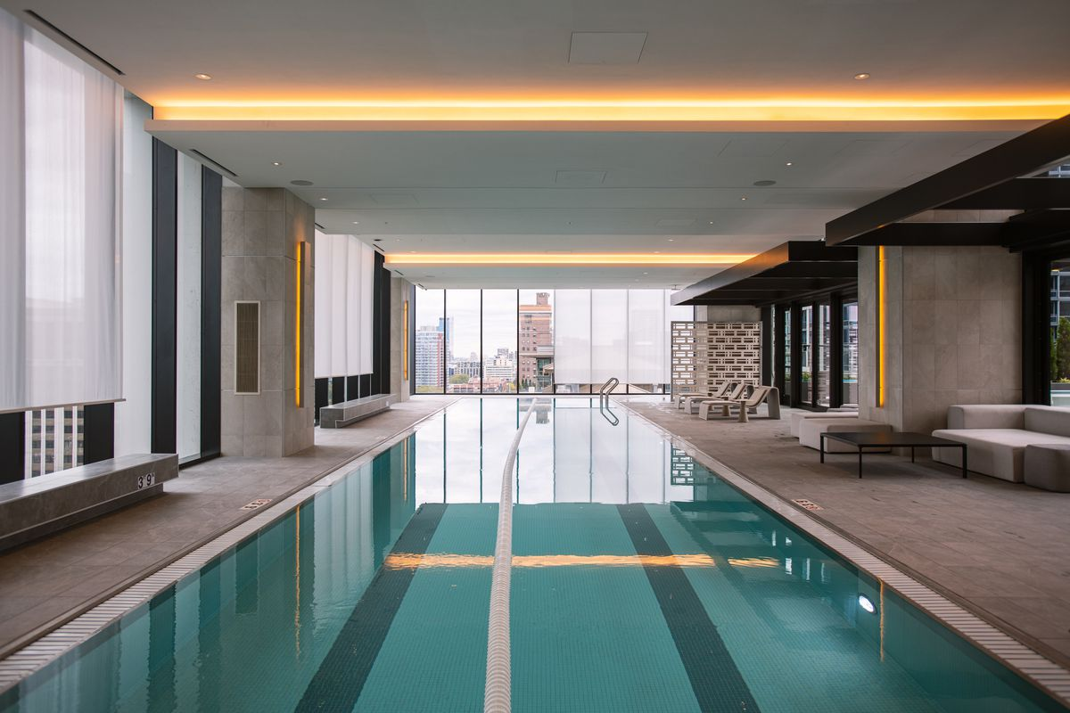 A two-lane lap pool surrounded by windows dressed in translucent roller shades.