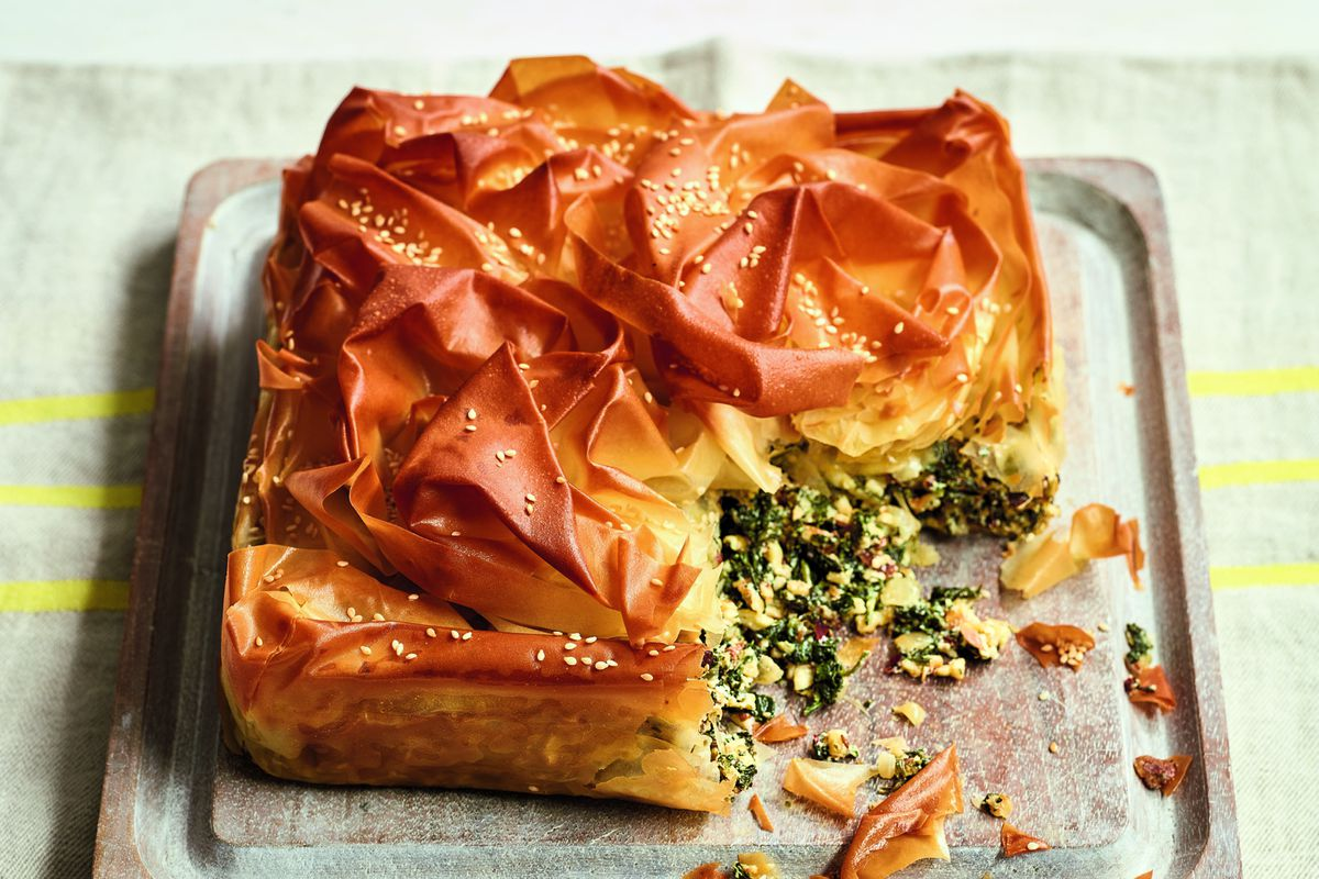 A square spanakopita pie with spinach spilling out
