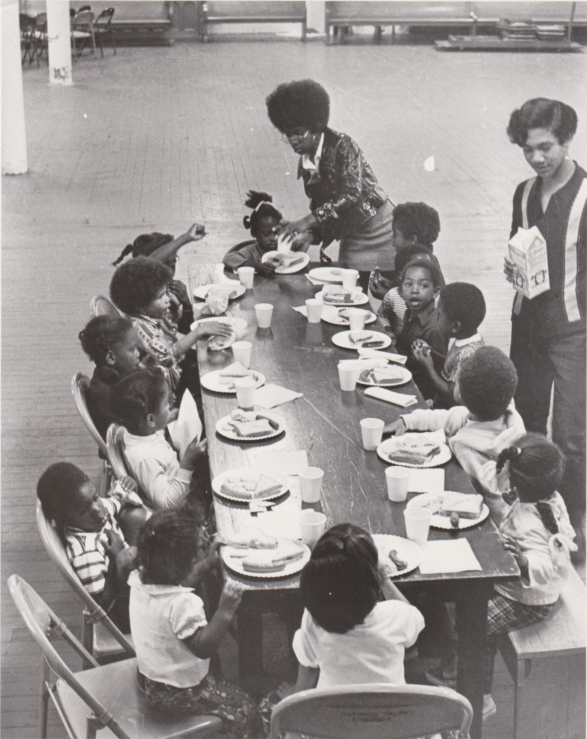 Children sit around a long table, eating breakfast.