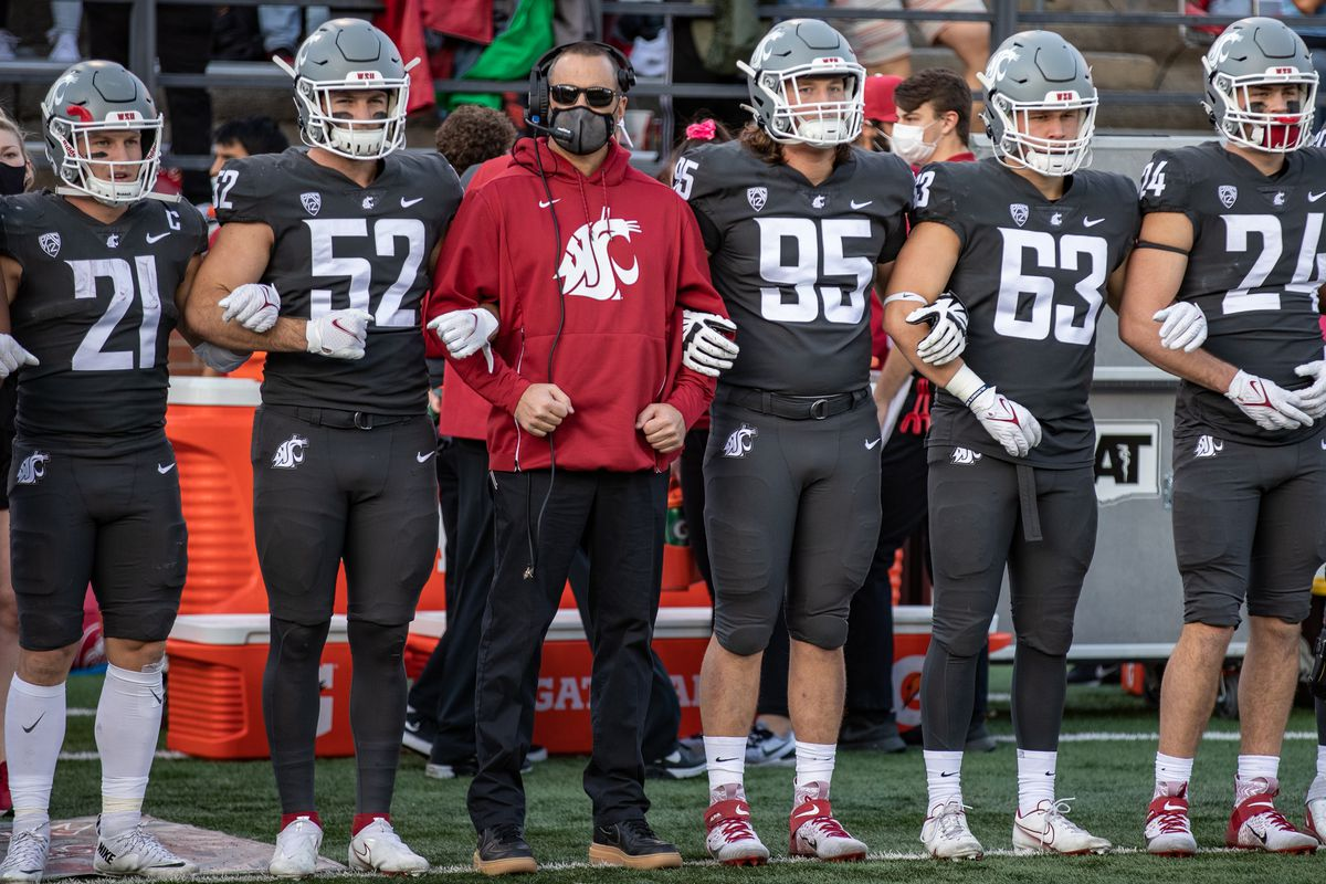 PULLMAN, WA - OCTOBER 16: Washington State head coach Nick Rolovich locks arms with teammates prior to a PAC 12 conference matchup between the Stanford Cardinal and the Washington State Cougars on October 16, 2021, at Martin Stadium in Pullman, WA.