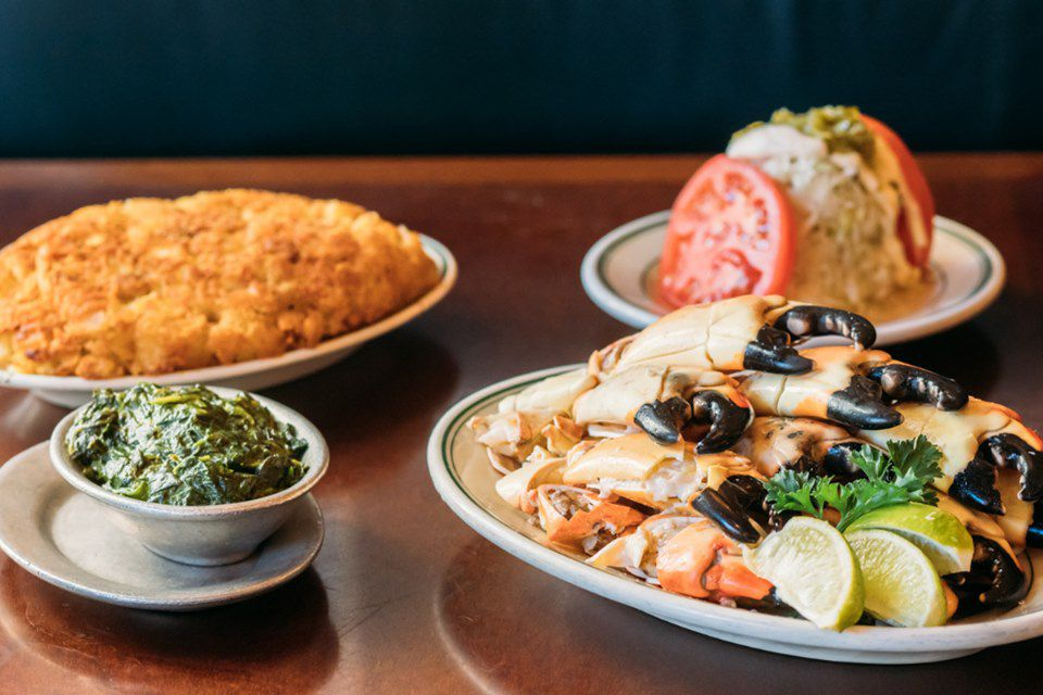 food plates with spinach, tomatoes, hash browns, and stone crabs on a wood table