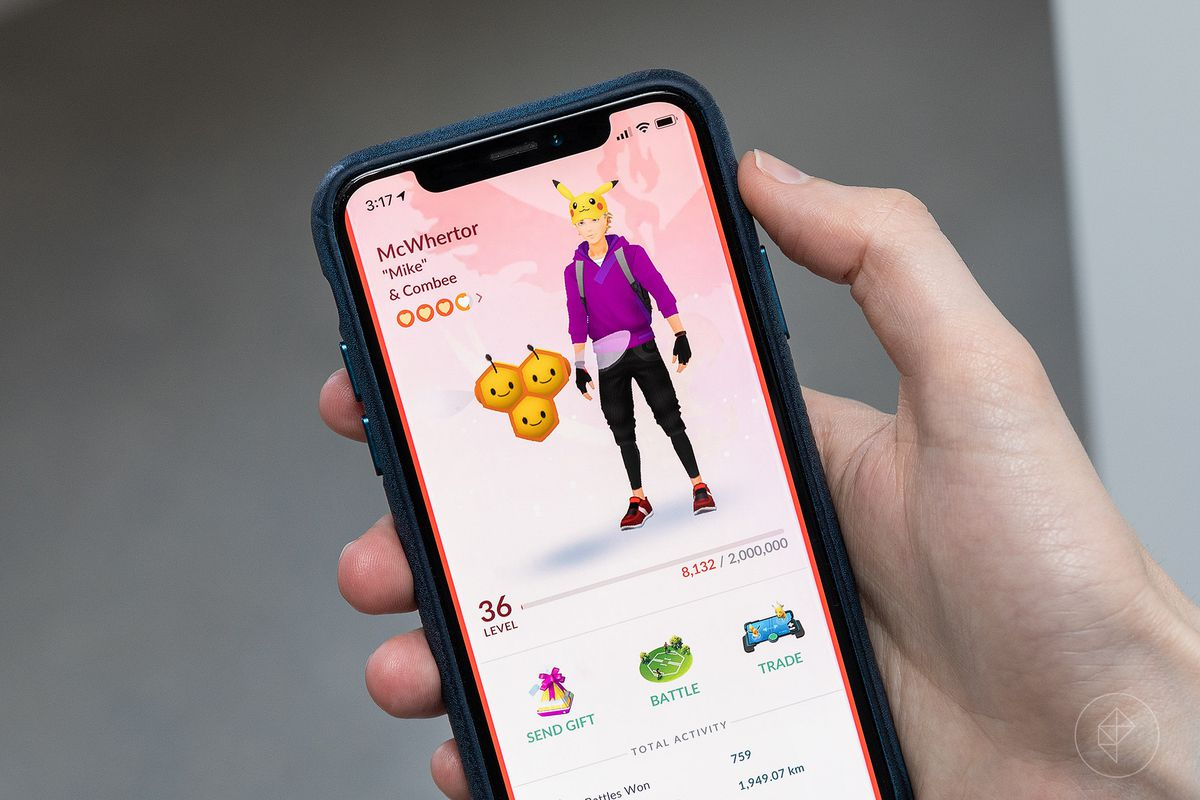 A hand holds an iPhone playing Pokemon Go, displaying the player profile screen