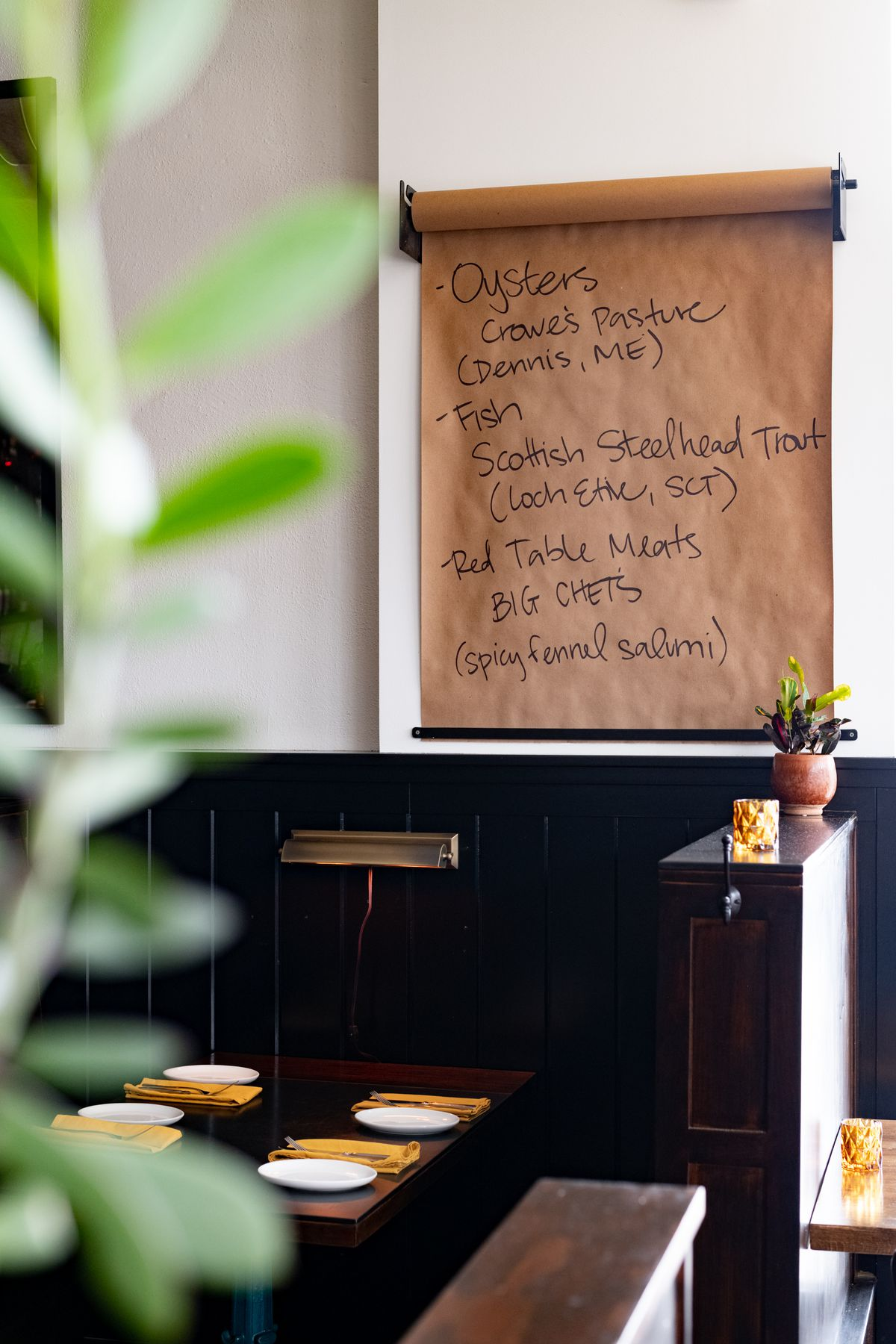 A dark brown wood booth set for four with bright, mustard-colored cloth napkins. Above it is a butcher paper specials listing the variety of mussels, fish, and salumi offered that day.