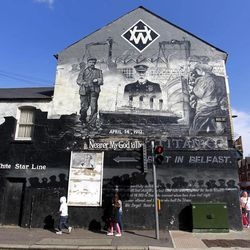 People walk past a mural of the Titanic in the Newtownards Road area of East Belfast, Northern Ireland, Friday, April 13, 2012.