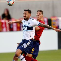 Real Salt Lake midfielder Damir Kreilach (8) watches the ball go into the goal as he and Vancouver Whitecaps defender Erik Godoy (22) jockey for position as Real Salt Lake and Vancouver FC play at Rio Tinto Stadium in Sandy on Wednesday, July 7, 2021.