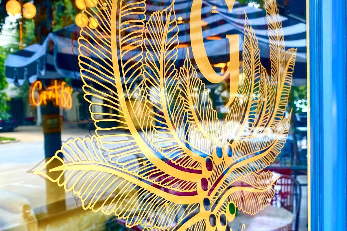 The glass front window of a restaurant with a gold logo on it. The logo is the letter G with feathers or some kind of leaf surrounding it