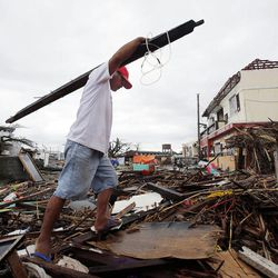 Tony Ballais, who lost his home in a typhoon, carries building materials through rubble in Tacloban, Friday, Nov. 22, 2013.