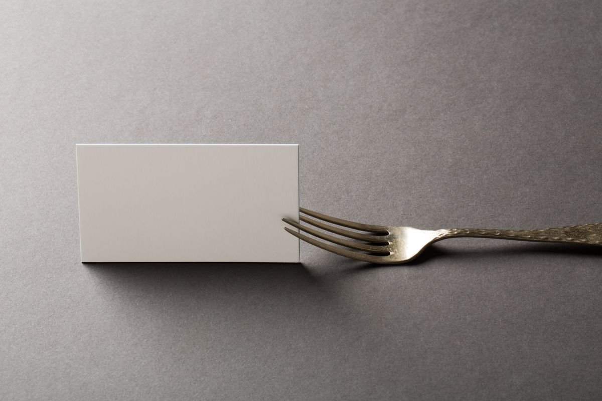 A blank card being picked up by a fork against a gray background.