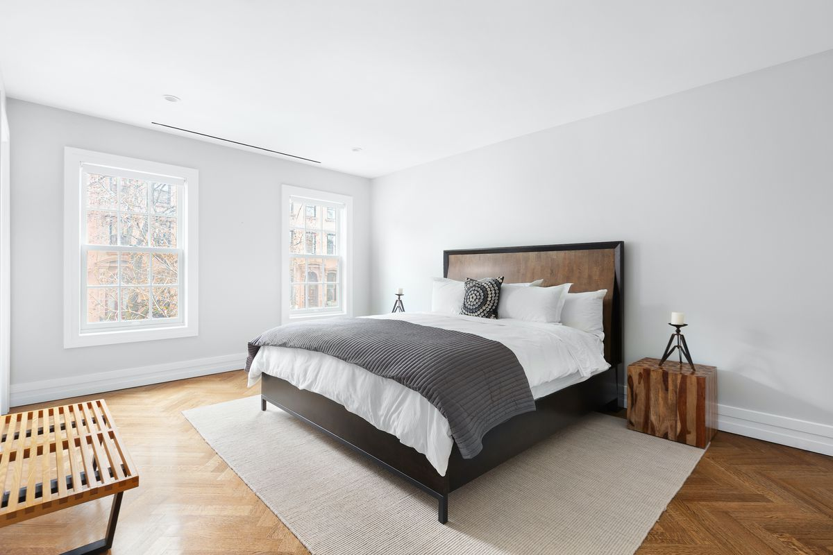 A bedroom with white walls, two windows, and wood floors. There is a bed with a wood frame, and a wooden nightstand.