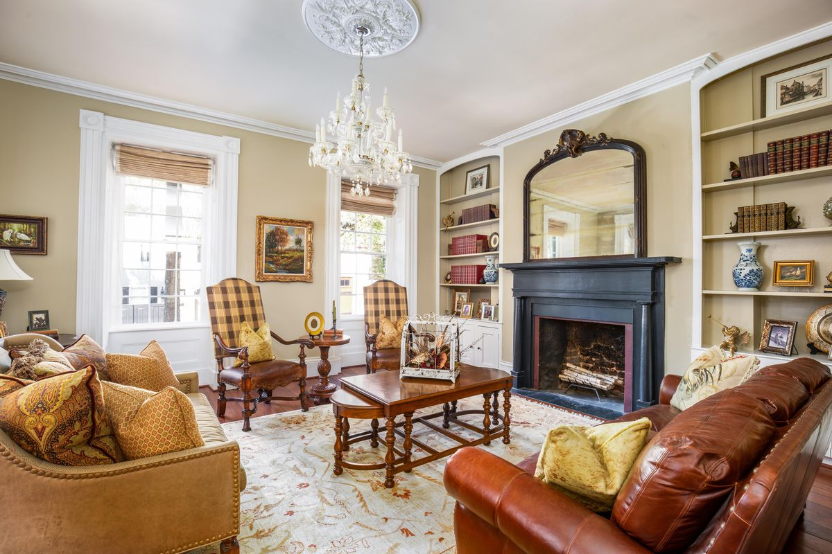 A sitting room has large windows, a black fireplace, and formal seating.