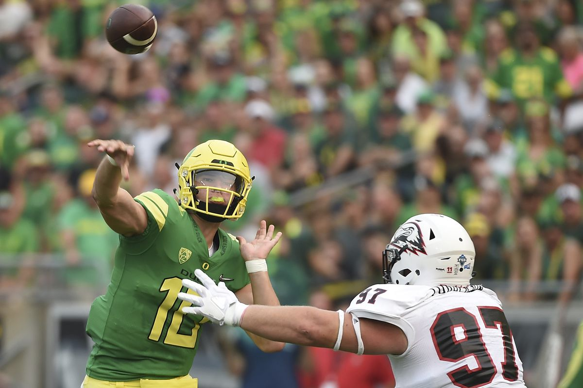 Quarterback Justin Herbert #10 of the Oregon Ducks throws a touchdown pass as defensive lineman Robert Torgerson #97 of the Southern Utah Thunderbirds applies pressure in the first quarter of the game at Autzen Stadium on September 2, 2017 in Eugene, Oregon.