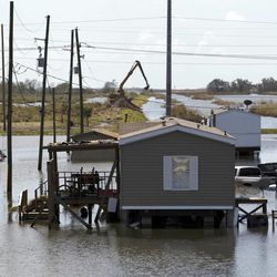 Trucks are flooded in receding flood waters from Hurricane Isaac along Louisiana Hwy 23 near West Point a La Hache, La., in Plaquemines Parish  Monday, Sept. 3, 2012.