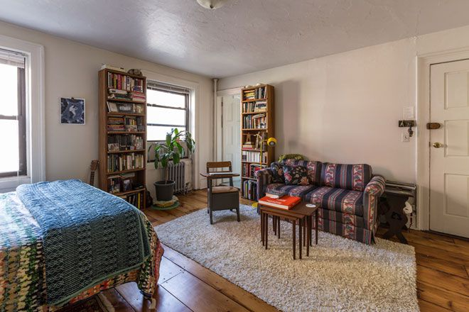 A living area with a patterned couch, table, chair, bed with patterned bed linens, bookcases, and windows.