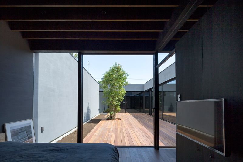 A bedroom looking out onto the courtyard and the living spaces behind glass walls on the other side.