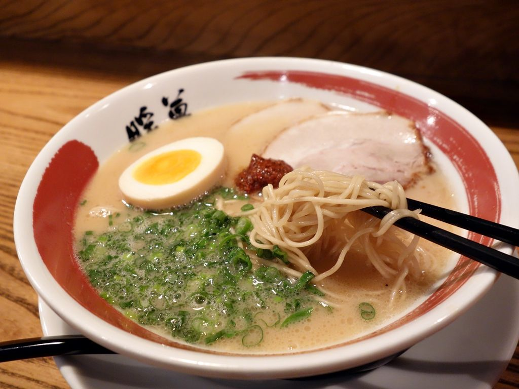 A bowl of tonkotsu ramen with pork, egg, and scallions, and a pair of chopsticks lifting up noodles.