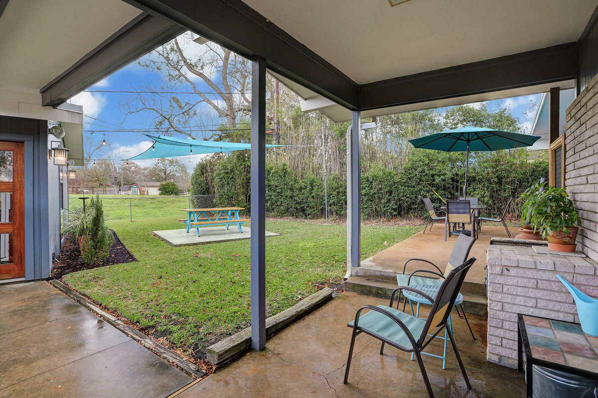 A backyard features a covered patio with chairs, and two dining areas—one picnic table and one other table.