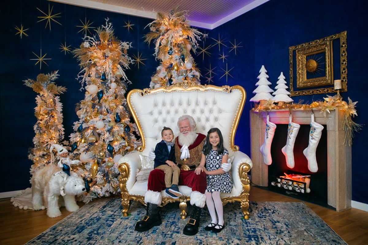Santa sitting in a white chair flanked by a young boy and girl.