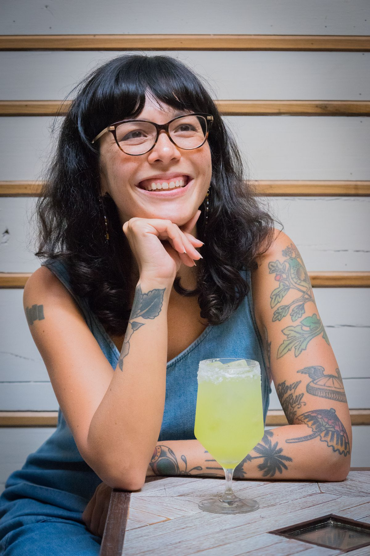 Claire Sprouse, owner of Hunky Dory, sits in blue overalls besides a green-yellow cocktail on ice.