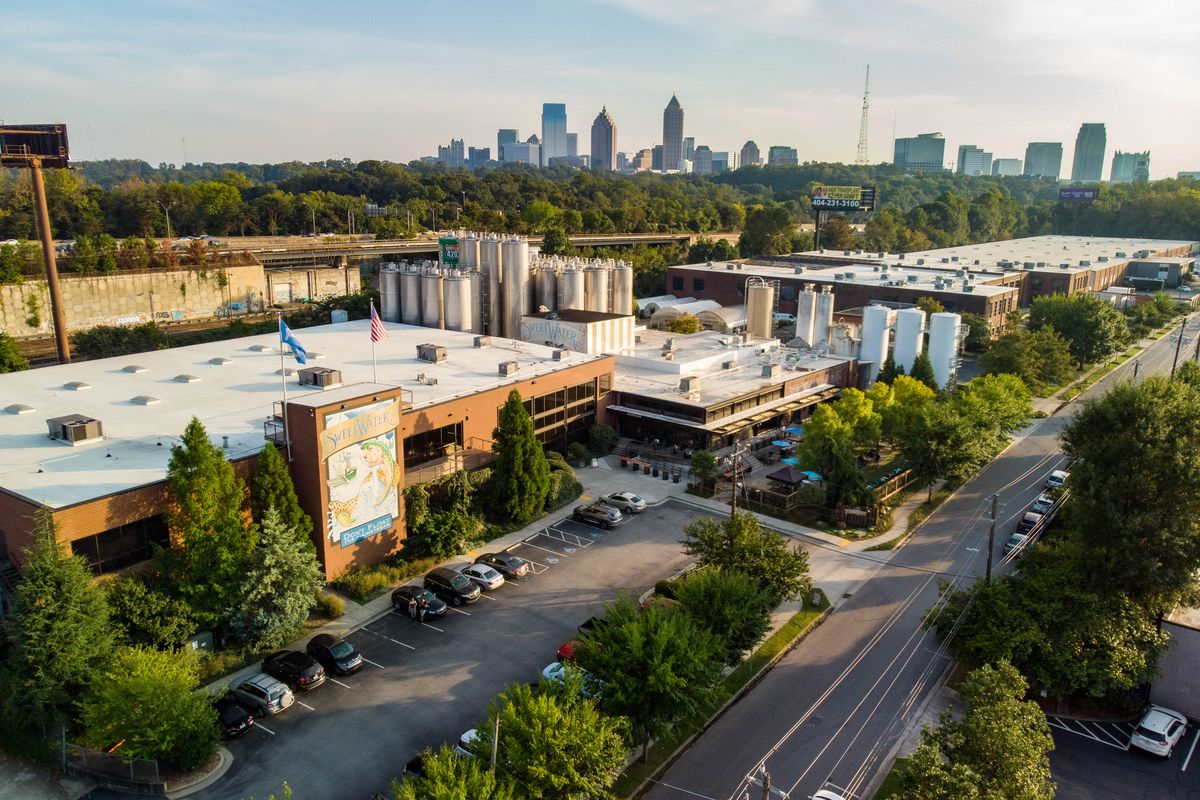 A drone shot of the Sweetwater Brewing complex with the Atlanta skyline in the background