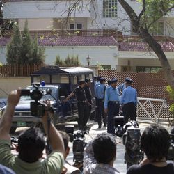 Pakistani police officers secure the area around the house where Osama bin Laden's family are being detained in Islamabad, Pakistan on Monday, April 2, 2012. The lawyer for Osama bin Laden's family says a Pakistani court has convicted his three widows and two of his daughters on charges of illegally living in Pakistan and sentenced them to 45-days in prison.